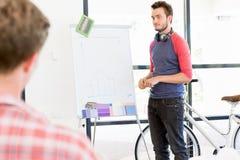 Περιστασιακός επιχειρηματίας που κάνει μια παρουσίαση στο γραφείο Στοκ φωτογραφία με δικαίωμα ελεύθερης χρήσης