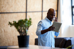 Περιστασιακός επιχειρηματίας που καλεί και που φαίνεται ο υπολογιστής ταμπλετών του Στοκ Φωτογραφία