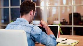 Περιστασιακός επιχειρηματίας που πίνει το καυτό ποτό μπροστά από το φορητό προσωπικό υπολογιστή φιλμ μικρού μήκους