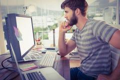 Περιστασιακός επιχειρηματίας που φαίνεται υπολογιστής στην αρχή Στοκ Εικόνα