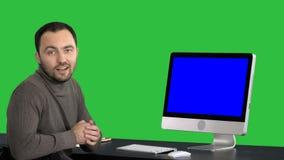 Περιστασιακός επιχειρηματίας που χαμογελά και που μιλά στη κάμερα που παρουσιάζει κάτι στο όργανο ελέγχου του υπολογιστή σε μια π φιλμ μικρού μήκους