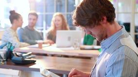 Περιστασιακός επιχειρηματίας που χρησιμοποιεί τον υπολογιστή ταμπλετών με τους συναδέλφους του πίσω από τον απόθεμα βίντεο