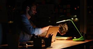 Περιστασιακός επιχειρηματίας που χρησιμοποιεί το lap-top και τη κάμερα τη νύχτα απόθεμα βίντεο