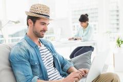 Περιστασιακός επιχειρηματίας που χρησιμοποιεί το lap-top στον καναπέ Στοκ φωτογραφία με δικαίωμα ελεύθερης χρήσης