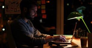 Περιστασιακός επιχειρηματίας που χρησιμοποιεί το lap-top τη νύχτα απόθεμα βίντεο