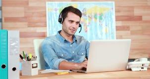 Περιστασιακός επιχειρηματίας χρησιμοποιώντας το lap-top και έχοντας τη συνομιλία με την κάσκα φιλμ μικρού μήκους