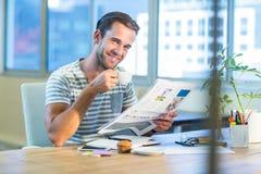 Περιστασιακός καφές κατανάλωσης επιχειρηματιών και ανάγνωση του περιοδικού στο γραφείο του στοκ εικόνες