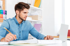 Περιστασιακός νέος επιχειρηματίας που εξετάζει το lap-top και που εργάζεται με τα έγγραφα Στοκ Εικόνες