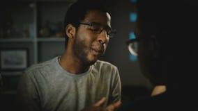Περιστασιακός νεαρός άνδρας αφροαμερικάνων στα γυαλιά που τρώει την πίτσα στο κόμμα Οι ευτυχείς φίλοι απολαμβάνουν το γρήγορο φαγ απόθεμα βίντεο