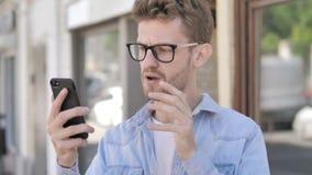 Περιστασιακός νεαρός άνδρας που ανατρέπεται από την απώλεια σε Smartphone στεμένος υπαίθριος απόθεμα βίντεο