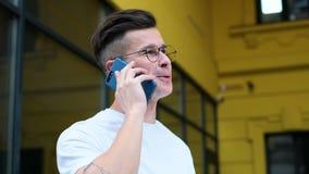 Περιστασιακός νεαρός άνδρας που χρησιμοποιεί το smartphone Πορτρέτο του ατόμου που μιλά στο smartphone που χαμογελά την ευτυχή φο φιλμ μικρού μήκους