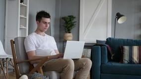 Περιστασιακός νεαρός άνδρας συνεδρίασης που εργάζεται στο lap-top απόθεμα βίντεο
