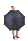 Περιστασιακός νεαρός άνδρας πίσω από μια μαύρη ομπρέλα Στοκ Εικόνες