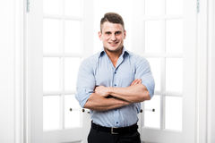 Περιστασιακός νεαρός άνδρας πορτρέτου που στέκεται στο εγχώριο εσωτερικό πορτών στο ελαφρύ υπόβαθρο που χαμογελά και που κοιτάζει στοκ φωτογραφία