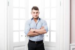 Περιστασιακός νεαρός άνδρας πορτρέτου που στέκεται στο εγχώριο εσωτερικό πορτών στο ελαφρύ υπόβαθρο που χαμογελά και που κοιτάζει στοκ εικόνες