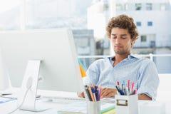 Περιστασιακός νεαρός άνδρας που χρησιμοποιεί τον υπολογιστή στο φωτεινό γραφείο Στοκ φωτογραφία με δικαίωμα ελεύθερης χρήσης