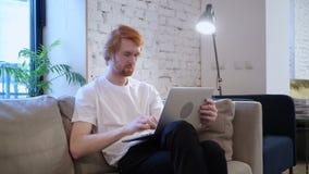 Περιστασιακός σχεδιαστής που εργάζεται με το lap-top στην περιτύλιξή του, γενειάδα φιλμ μικρού μήκους