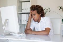 Περιστασιακός τονισμένος επιχειρηματίας που εξετάζει τον υπολογιστή του Στοκ φωτογραφία με δικαίωμα ελεύθερης χρήσης