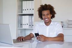 Περιστασιακός χαμογελώντας επιχειρηματίας που χρησιμοποιεί το smartphone και το lap-top του στο γραφείο του Στοκ φωτογραφίες με δικαίωμα ελεύθερης χρήσης