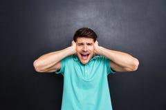 Περιστασιακό άτομο που καλύπτει τα αυτιά του και που φωνάζει πέρα από το μαύρο υπόβαθρο Στοκ φωτογραφία με δικαίωμα ελεύθερης χρήσης