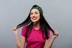 Περιστασιακό κορίτσι ΚΑΠ εφήβων ύφους γυναικών στην επικεφαλής μακρυμάλλη τοποθέτηση σε πράσινο Ύφος νεολαίας πλάνο μόδας Στοκ Φωτογραφίες