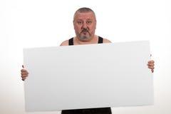 Περιστασιακό παχύ άτομο που κρατά ένα κενό έγγραφο πέρα από ένα άσπρο υπόβαθρο Στοκ Φωτογραφία