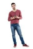 Περιστασιακό όμορφο μοντέρνο άτομο που κρατά το κινητό τηλέφωνο εξετάζοντας τη κάμερα Στοκ Φωτογραφίες