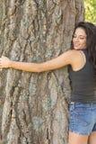 Περιστασιακό όμορφο brunette που αγκαλιάζει ένα δέντρο με τις ιδιαίτερες προσοχές Στοκ Εικόνα