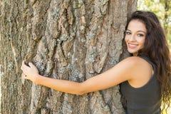 Περιστασιακό όμορφο brunette που αγκαλιάζει ένα δέντρο που εξετάζει τη κάμερα Στοκ Εικόνες