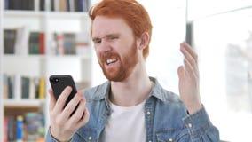 Περιστασιακό Redhead άτομο που αντιδρά στην απώλεια σε Smartphone απόθεμα βίντεο