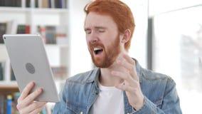 Περιστασιακό Redhead άτομο που αντιδρά στην απώλεια χρησιμοποιώντας την ταμπλέτα απόθεμα βίντεο