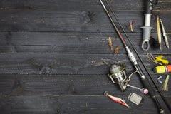 Περιστρεφόμενα ράβδος και εξέλικτρο, εξοπλισμός αλιείας στο μαύρο ξύλινο υπόβαθρο στοκ φωτογραφία με δικαίωμα ελεύθερης χρήσης