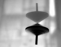 Περιστρεφόμενη κορυφή στη δράση σε μια επιφάνεια καθρεφτών, καμία βαρύτητα Στοκ Φωτογραφίες