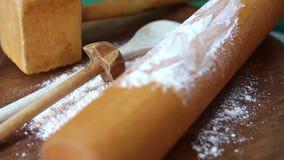 Περιστρεφόμενος ξύλινος πίνακας με το μαγείρεμα του κουταλιού και του κυλίνδρου και του αλευριού ζύμης φιλμ μικρού μήκους