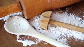 Περιστρεφόμενος ξύλινος πίνακας με το μαγείρεμα του κουταλιού και του κυλίνδρου και του αλευριού ζύμης απόθεμα βίντεο