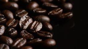 Περιστρεφόμενος πυροβολισμός των εύγευστων, ψημένων φασολιών καφέ σε μια άσπρη επιφάνεια απόθεμα βίντεο