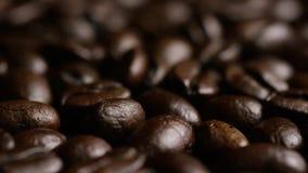 Περιστρεφόμενος πυροβολισμός των εύγευστων, ψημένων φασολιών καφέ σε μια άσπρη επιφάνεια φιλμ μικρού μήκους
