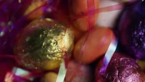 Περιστρεφόμενος πυροβολισμός των ζωηρόχρωμων καραμελών Πάσχας σε ένα κρεβάτι της χλόης Πάσχας φιλμ μικρού μήκους