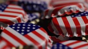 Περιστρεφόμενος πυροβολισμός των καλυμμάτων μπουκαλιών με τη αμερικανική σημαία που τυπώνεται σε τους απόθεμα βίντεο