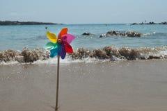 Περιστρεφόμενο ζωηρόχρωμο ουράνιο τόξο pinwheel στην ακτή παραλιών Στοκ φωτογραφίες με δικαίωμα ελεύθερης χρήσης