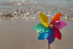 Περιστρεφόμενο ζωηρόχρωμο ουράνιο τόξο pinwheel στην παραλία Στοκ εικόνα με δικαίωμα ελεύθερης χρήσης