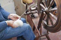 Περιστρεφόμενο μαλλί ατόμων σε μια παραδοσιακή περιστρεφόμενη ρόδα. Στοκ Εικόνες