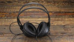 περιστροφή Ακουστικά με το καλώδιο που στέκεται σε ένα ξύλινο γραφείο απόθεμα βίντεο
