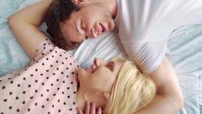 Περιστροφή καμερών πέρα από το καλό ζεύγος που βρίσκεται στο κρεβάτι πρόσωπο με πρόσωπο με το ζουμ έξω απόθεμα βίντεο