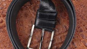 Περιστροφή, κινηματογράφηση σε πρώτο πλάνο μιας μαύρης ζώνης, που βρίσκεται σε ένα καφετί δέρμα κροκοδείλων φιλμ μικρού μήκους