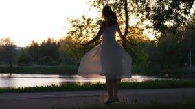 Περιστροφή κοριτσιών γύρω στο αερώδες φόρεμα ενάντια στη ρύθμιση του ήλιου φιλμ μικρού μήκους