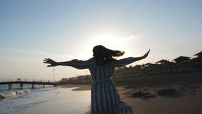Περιστροφή κοριτσιών με τον ενθουσιασμό στον ήλιο στην παραλία απόθεμα βίντεο