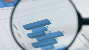 περιστροφή Μελετώντας τα διαγράμματα με μια ενίσχυση - γυαλί οικονομική εργασία εκθέσεων επιχειρηματιών απόθεμα βίντεο
