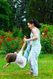 Περιστροφή μητέρων και γιων στο θερινό πάρκο στοκ φωτογραφία με δικαίωμα ελεύθερης χρήσης