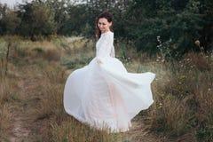 Περιστροφή νυφών του Yong σε ένα άσπρο φόρεμα στην τράπεζα στη φύση στοκ φωτογραφία με δικαίωμα ελεύθερης χρήσης
